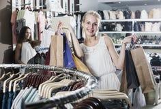 2 девушки покупая верхние части в магазине одежд Стоковая Фотография RF