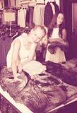2 девушки покупая верхние части в магазине одежд Стоковая Фотография