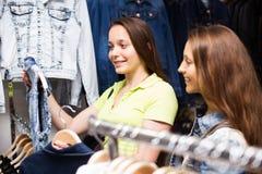 2 девушки покупая жилет в магазине Стоковая Фотография