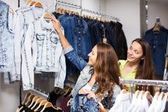 2 девушки покупая жилет в магазине Стоковое Фото