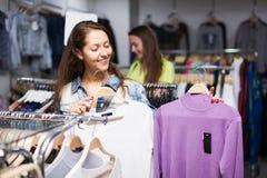 2 девушки покупая свитер в магазине Стоковое Изображение RF