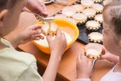 2 девушки помогли маме полить бэттер в прессформы для пирожных Стоковые Изображения RF