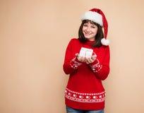 девушки подарка рождества предпосылки удерживание шлема красивейшей милой счастливое изолировало смотреть присутствующий santa по Стоковое фото RF