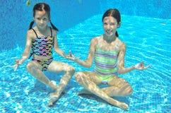 2 девушки подводной в бассейне Стоковое Изображение