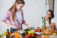 2 девушки подготавливая обедающий в концепции кухни Стоковая Фотография RF