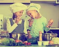 2 девушки подготавливая овощи и усмехаясь внутри помещения Стоковые Изображения