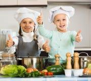 2 девушки подготавливая овощи и усмехаясь внутри помещения Стоковые Фото