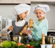 2 девушки подготавливая овощи и усмехаясь внутри помещения Стоковые Фотографии RF
