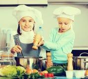 2 девушки подготавливая овощи и усмехаясь внутри помещения Стоковая Фотография