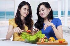 2 девушки подготавливая салат овощей Стоковое фото RF