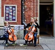 2 девушки подростка выполняют классическую музыку с виолончелями в Мюнхене Стоковое Фото