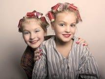 2 девушки подростка играя домохозяек, делают стили причёсок и состав имея потеху Стоковое фото RF