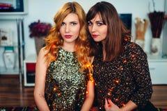 2 девушки празднуя ` s Eve рождества или Нового Года дома Стоковые Фотографии RF