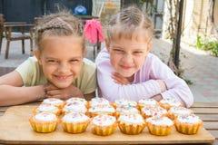 2 девушки претендуя смешные стороны, сидя перед пирожными Стоковые Изображения RF