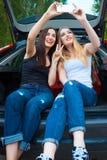 2 девушки представляя в автомобиле Стоковые Фотографии RF
