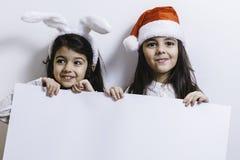 2 девушки представляя на праздники рождества и Нового Года Стоковые Фотографии RF