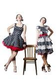 2 девушки представляя стоять, полагаясь на стуле Стоковая Фотография RF