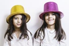 2 девушки представляя с желтыми и розовыми сияющими шляпами Стоковые Изображения