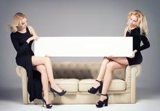 2 девушки представляя с пустой доской Стоковая Фотография RF