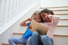 2 девушки представляя для Selfie на таблетке цифров дома Стоковые Фотографии RF