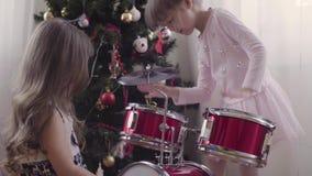2 девушки приближают к рождественской елке играя набор барабанчика Стоковые Фотографии RF