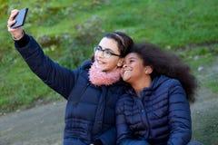 2 девушки принимая фото с чернью Стоковая Фотография