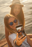 2 девушки принимая Selfie около реки Стоковые Фотографии RF