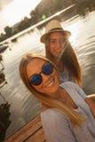 2 девушки принимая Selfie около реки Стоковая Фотография