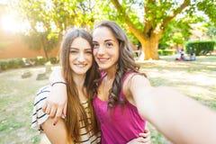 2 девушки принимая selfie совместно на парк Стоковое Изображение