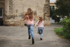 2 девушки при длинные волосы бежать прочь Стоковая Фотография