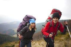 2 девушки при рюкзаки приходя через лес Стоковое Изображение