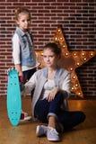 2 девушки при скейтборд сидя в студии Стоковые Фотографии RF