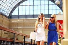 2 девушки при солнечные очки принимая фото с smartphone Стоковые Изображения RF