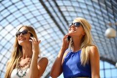 2 девушки при солнечные очки принимая фото с smartphone Стоковая Фотография RF