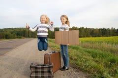 2 девушки при чемодан стоя о дороге Стоковые Фотографии RF