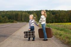2 девушки при чемодан стоя о дороге Стоковое фото RF