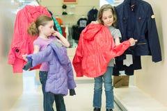 2 девушки пробуют дальше одежды в магазине Стоковые Изображения RF