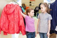 2 девушки пробуют дальше одежды в современном магазине Стоковое фото RF