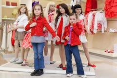 2 девушки пробуя на красных одеждах вместе с манекенами Стоковые Фотографии RF