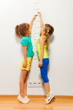 2 девушки протягивают вверх с рукой на масштабе Стоковая Фотография