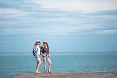 2 девушки путешествуют вдоль seashore Стоковое Изображение RF