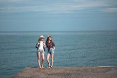 2 девушки путешествуют вдоль seashore Стоковые Изображения