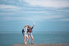 2 девушки путешествуют вдоль seashore Стоковое Изображение