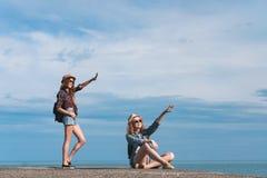 2 девушки путешествуют вдоль seashore Стоковая Фотография RF