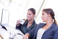2 девушки работая на компьтер-книжке Стоковое Изображение RF