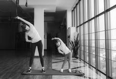 2 девушки различных времен делая йогу Стоковая Фотография