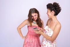 2 девушки различных гонок имея потеху с smrtfonom Интернет, сообщение, приятельство Стоковые Изображения RF