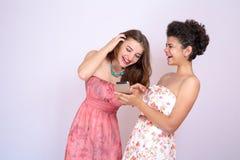 2 девушки различных гонок имея потеху с smrtfonom Интернет, сообщение, приятельство Стоковая Фотография RF
