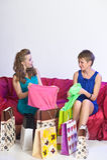 2 девушки рассматривают и показывают приобретения одина другого Стоковое фото RF