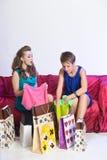 2 девушки рассматривают и показывают приобретения одина другого Стоковая Фотография